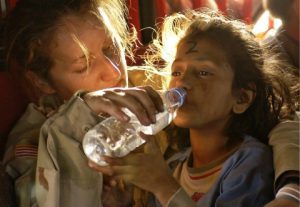A child getting help from a female army officer to drink water in a disaster scene.