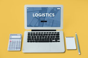 a laptop, calculator, a notepad and a pen to illustrate the concept of logistics and procurement